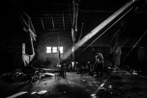 Refugees sweeping floor inside a temporary shelter, despite the conditions in which they are, they try to keep the place in good condition.  Belgrade, Serbia.