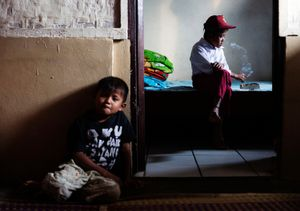 Ilham Hadi, who has smoked up to two packs a day and began when he was four years old, wears his third grade uniform while smoking in his bedroom as his younger brother looks on in their village near the town of Sukabumi. © Michelle Siu