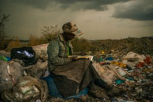 1st Prize Contemporary Issues Single © Micah Albert, USA, Redux Images. 03 April 2012, Nairobi, Kenya. Pausing in the rain, a woman working as a trash picker at the 30-acre dump, which literally spills into households of one million people living in nearby slums, wishes she had more time to look at the books she comes across. She even likes the industrial parts catalogs.