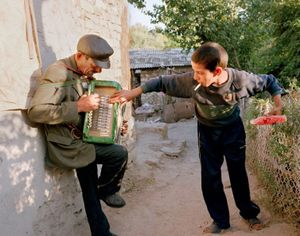 "Yanush helps his grandfather play the broken accordion. Yampil, Ukraine, 2005. From the series ""From the Mountains and to the Sea"" © Nadia Sablin"