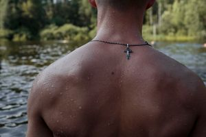 "Dmitri (Dima) Antonets (17) escapes the heat during an afternoon off at the lake. 31 July 2016, Diveevo, Russia. He wears a Russian Orthodox cross for safety during his travels from Stavropol to Diveevo. ""Orthodox Warrior"" camp takes place in Diveevo, the center of pilgrimage for Orthodox Christians in Russia."