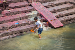 A street child sifts through the run off water from a recent cremation at Pashupati temple, the world's largest outdoor crematorium.