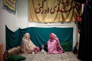While waiting for the communal dinner to be served, two women talk at the Islamic Centre Imam Mahdi, near Furio Camillo, southern Rome.