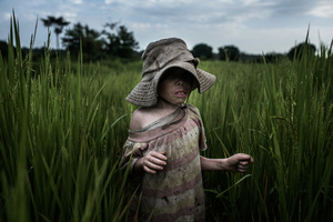 Semabulia plays in the rice field where the kids spend most of their time. His wide-rimmed hat protects his skin from the sun during the day