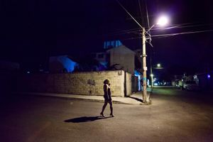 Reyna Patricia walking in the night looking for clients. © Meeri Koutaniemi