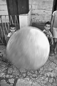 Twins playing with a ball hit the photographer's camera and as a result, the camera hits the photographer's head. They live near the San Lazaro Sanctuary in the suburbs of Havana, Boyeros Municipality.