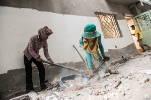 Two female workers clear up debris from the building site, many of the female workers are given menial tasks such as cleaning.