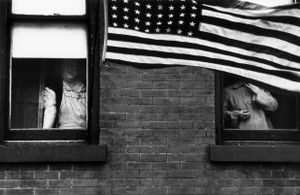 "Parade, Hoboken, New Jersey, 1955. From ""The Americans."" © Robert Frank. Published by Robert Delpire, then Grove Press, and most recently reprinted by Steidl."