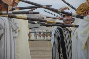 A rifleman peers out amongst the group enacting a traditional warriors gun dance. Tissa, Morocco