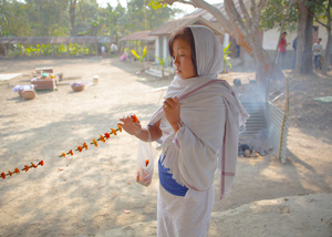 A girl strings flowers as an offering to the sylvan deities of the Umang Lai.
