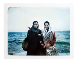 Two young refugee women posing for a portrait soon after their arrival on Lesvos. The girl on the right is still wearing the emergency blanket given to her after reaching the shore to keep her body temperature stable. Skala, Lesvos, Greece, January 2016.
