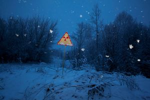 Near Pripyat, Ukraine, 2011. A radiation sign along the road warns of the danger. The tranquility of the sight on an evening of heavy snowfall belies the lingering threat in the peaceful winter landscape.