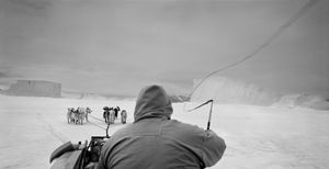 Greenland. Hunter cracking his whip on his dog sled. © Ragnar Axelsson