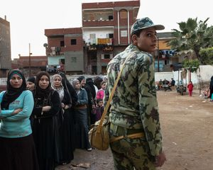 A soldier is directing the female queue during the second turn of the constitutional election vote in Kofrishich.   © Domenico D'Alessandro