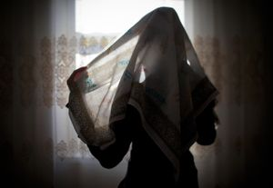 """A young Chechen girl wraps a pastel-colored head covering before leaving her home. In modern-day Chechnya, Islam is quickly becoming the cornerstone of identity for youth. From the series """"Goodbye My Chechnya."""" 2012"""