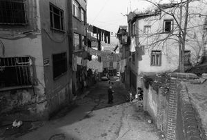 Laundry hangs out to dry on lines strung between two houses on opposite sides of a narrow street.