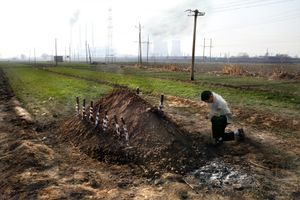 On the outskirts of Xingtai, Zhang Wei mourns his brother, a worker in the steel factory behind who died from lung cancer. The small local village has seen over 30 cancer related deaths in the past 15 years, making it one of the several unacknowledged Cancer Villages dotted around China. ©Souvid Datta