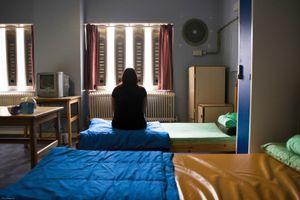 A female prisoner sitting on her bed in the first night  (4 person) dorm at HMP Holloway, the main female prison in London.