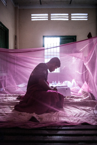 UXO salvage diver Lorn Sarath (25) sits underneath a mosquito net in the early hours of the morning at the divers barracks in Kampong Chhanang Province, Cambodia. The divers study English daily improving their ability to work regionally and train globally.