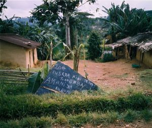 "A roadside sign reads, ""2014, what shall we say again? We ask for lasting peace."" Yet the Congolese government has been unsuccessful in its attempts to disarm the Kikuni faction of the RM. ""They [FARDC] give the FDLR arms... we can't give arms to FARDC so we store them,"" explains a soldier. To integrating into the FARDC, Kikuni responds, ""Not into an army of foreigners."" © Diana Zeyneb Alhindawi"