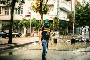 A far left-wing protester of PKK youth organisation YDG-H armed with stones during clashes with riot police at anti-government demonstration in Istanbul's Gazi neighborhood, Turkey.