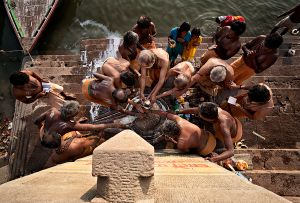 Varanasi, India: The early morning ritual on the shores of the sacred river of Ganges. Gift bearing to Shiva's lingam, hoping that the young girl will become fertile. © Matjaz Krivic