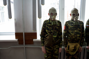 Students stand ready as a teacher observes how quickly they can dress in gask masks, 4 Apr 2016, School #7, Dmitrov, Russia. School #7 is a public school but offers cadet classes for those who wish to participate. The benefit of participating in cadet classes includes free lunch, while other students have to pay.