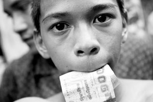 A boy with money in the mouth. After the boxing match, the winner goes around and collects money from tourists. But he is not allowed to keep the money, most of it takes the coach. © Sandra Hoyn