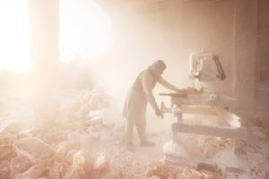 A salt carver cuts blocks of pink rock salt in to squares covering everything in fine salt dust outside the Khewra Salt mine.