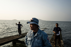 Divers Lorn Sarath, Sok Chenda and Brak Hean wait for a boat at the seaside town of Kep to take them to the island of Koh Seh to follow up on a report of UXO found on the island.
