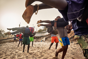 Young wrestlers train at the school of ex-Wrestler Boy Kaire at the Corniche in Dakar on April 3, 2015. Many young men dream of a career as a Wrestler. Because they do not have a lot of money, they mostly train with the easiest instruments. Here the wrestling trainees have to run through the sand, carrying each other.