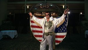 ELVIS IMPERSONATOR, FLAG CAPE <BR>At a ceremony marking the 25th anniversary of the death of Elvis Presley, thousands of impersonators converged on Memphis, Tennessee, to pay homage to their spiritual ancestor. © Peter Friedman and © Roger Manley