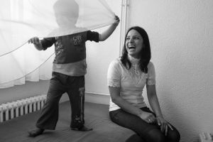 Sinem and her son Taylan, who are from Turkey, play in their room.  Both Sinen and her husband, Taylan, spent two years in prison in Turkey because of their Communist beliefs.  After their release, they received death threats.  © Alison McCauley