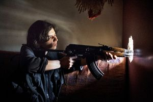 Rukan, a female YPG fighter and unit leader aims her weapon from a fighting position in the Sheikh Maqsood district in Aleppo on April 19, 2013. © Nish Nalbandian