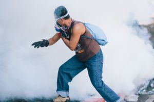 A protester running away from a tear gas canister during a stand-off between anti-Government protesters and police at Government House in Bangkok.