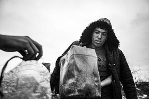 A people collect water in makeshift shelter near main train station  in Belgrade, Serbia.