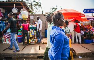 A man and woman walk past busy market stalls in Freetown.
