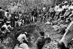 Onlookers surround the edge of a recently opened grave to watch the anthropologists work. The participation and collaboration of local people is vital to the exhumation. © Victor Blue, 2004
