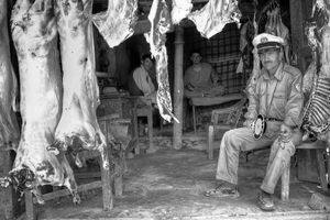 A policeman on foot patrol takes a short break in the shade of a local butcher shop.