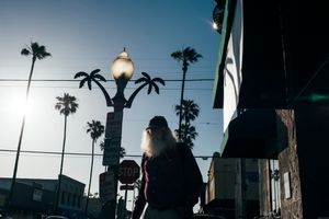 An old, bearded man walks down the street, surrounded by palm trees. Ocean Beach, San Diego.
