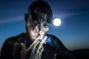 A mine worker takes a smoke break before going back into the pit. Miners in Bani face harsh conditions and exposure to toxic chemicals and heavy metals.Image taken in Bani, Burkina Faso, on 20 November 2015.