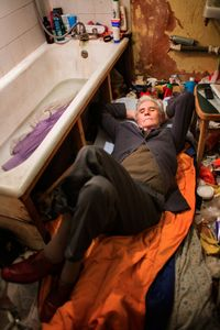 George is taking a rest on a sleeping bag on his bathroom floor. George slept here for one week since his bedroom was occupied by a long-term guest and his alternative sleeping space - a mattress in a doorframe - was taken by a friend in need. © Corinna Kern