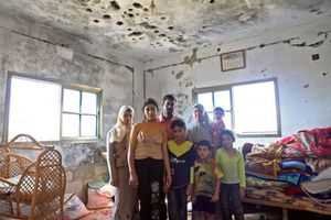 A Palestinian family poses for a portrait inside their damaged house, after the 2009 war on the Gaza Strip, 2009.