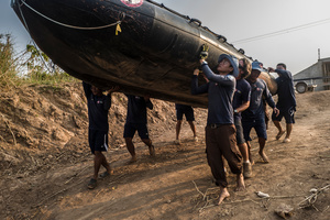 The diver team carry their inflatable boat down the banks of the Tonle Sap river.