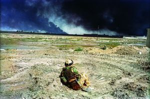 Basra April 7, 2003. A British soldier watches black smoke rising from the southern port city of Basra. The burning building on the right, a technical college, was repeatedly shelled by British forces in response to Iraqi sniper attacks. © Alan Chin