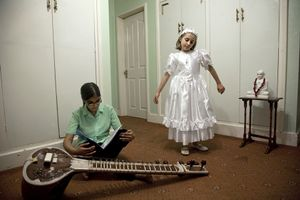 Jain and Catholic neighbours  Two young girls from different religious backgrounds play together. The Jain girl takes sitar lessons in her British school. The 7-year-old Catholic girl recently had her first Holy Communion and enjoys dressing in the traditional white dress she wore for the occasion. © Liz Hingley