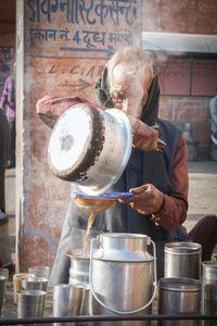 A tea seller prepares chai with milk