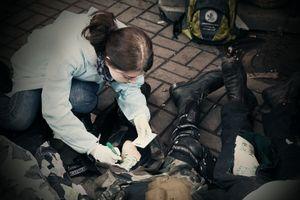 Volunteer nurse writing deadman`s name on the corpse leg (Ukraine, Kiev, February, 2014)