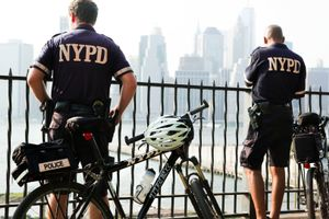Bicycle police, bank East River, Manhattan behind.