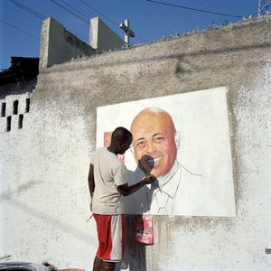 An artist hired by the Juvénat district support committee for the new president paints a portrait of Michel Joseph Martelly on Inauguration Day, Pétion-Ville. Haiti. 2011. © Paolo Woods/INSTITUTE